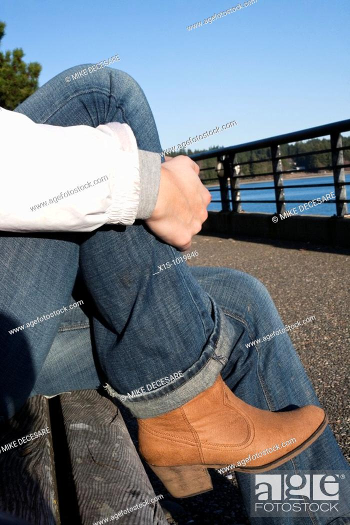 Stock Photo: Hip female boots and blue jeans emphasized in outdoor closeup that say relaxing in style.
