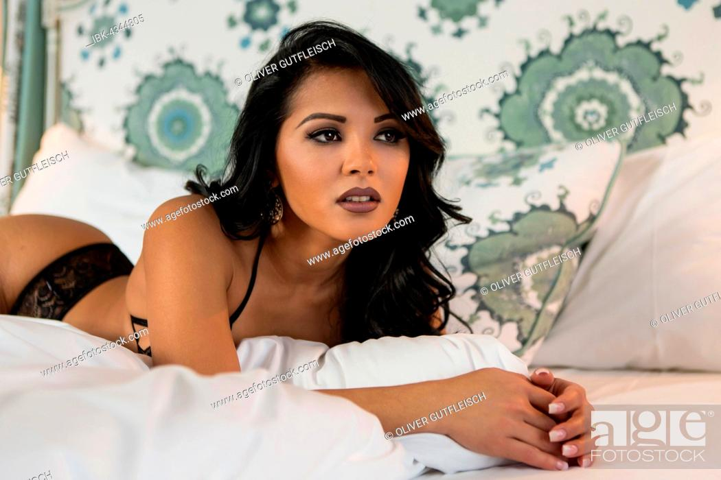 Stock Photo: Young woman in lingerie posing on bed, fashion, lifestyle.