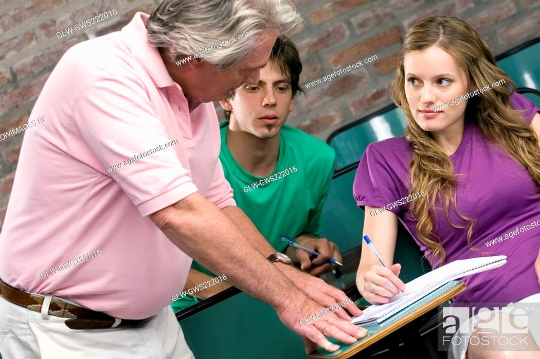 Stock Photo: Professor assisting his students in a classroom.