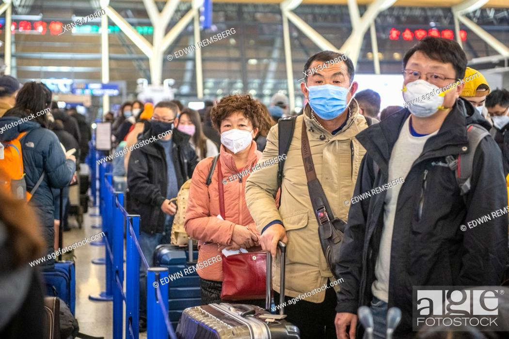 Stock Photo: Shanghai, China, 28th Jan 2020, People standing in line at the airport wear medical masks to prevent contracting the Coronavirus, Edwin Remsberg.