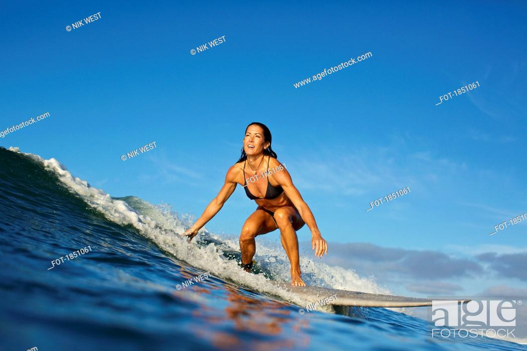 Stock Photo: Female surfer riding ocean wave.