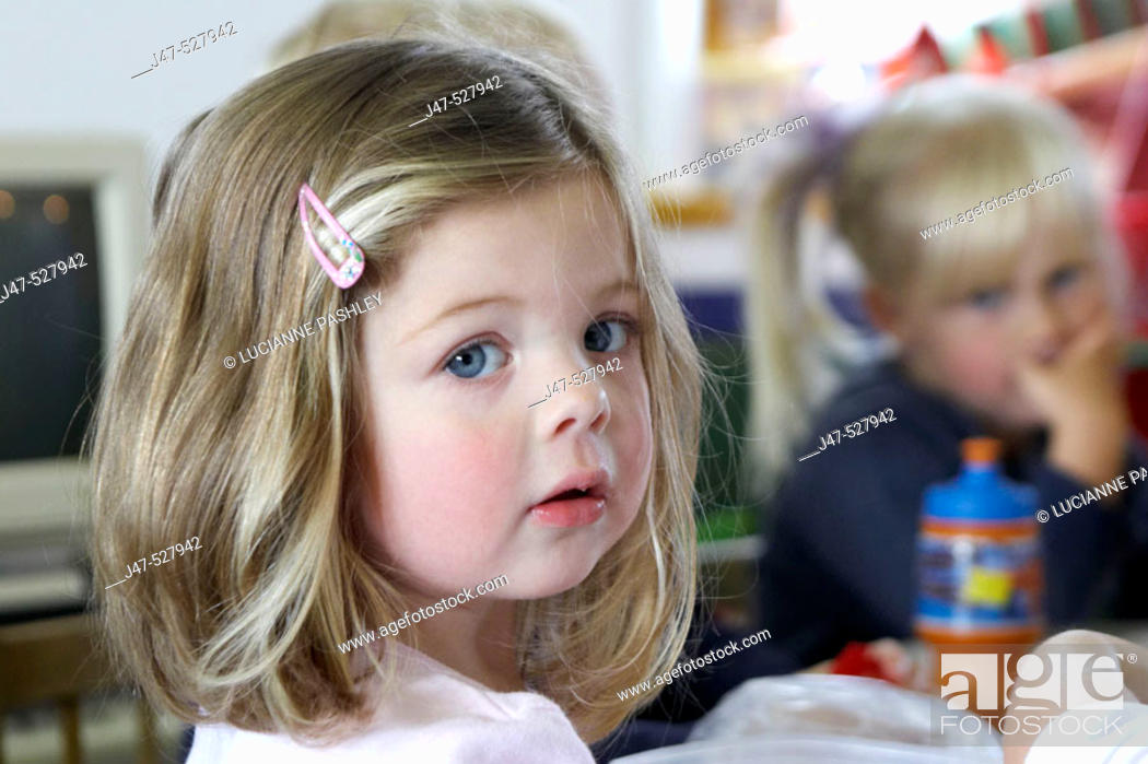 Stock Photo: 3 year old girl, looking into camera, at nursery, serious,.