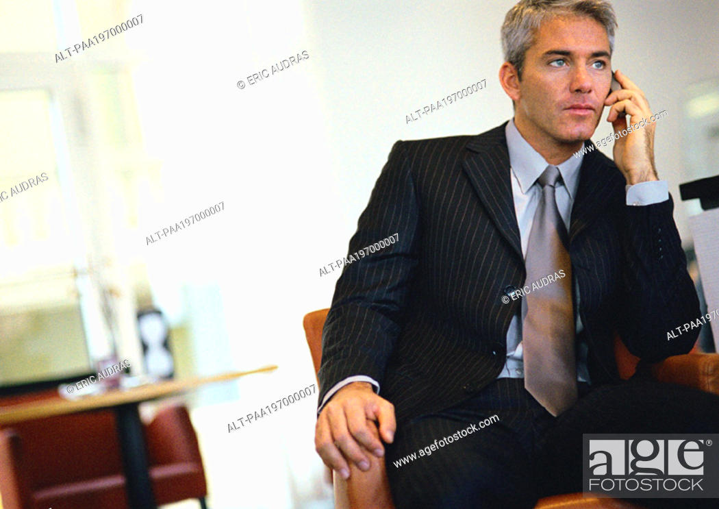 Stock Photo: Businessman sitting, talking on cell phone.