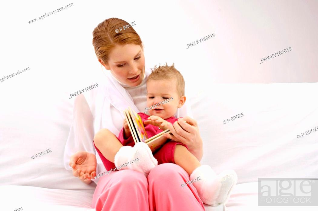 Stock Photo: Young woman showing a picture book to her son.