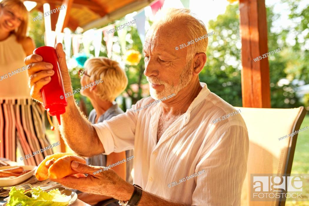 Stock Photo: Senior man preparing a hot dog on a garden party.