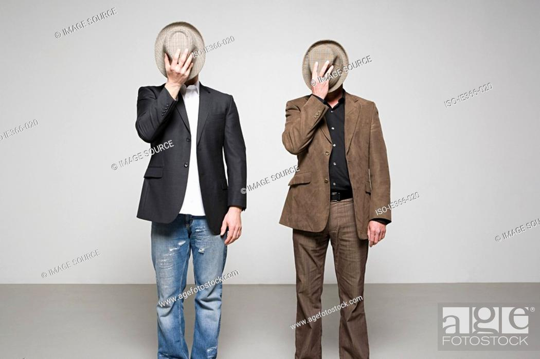 Stock Photo: Men holding hats over their faces.