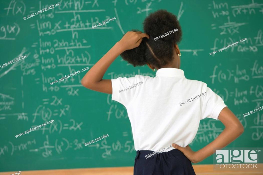Stock Photo: African American girl looking at blackboard.