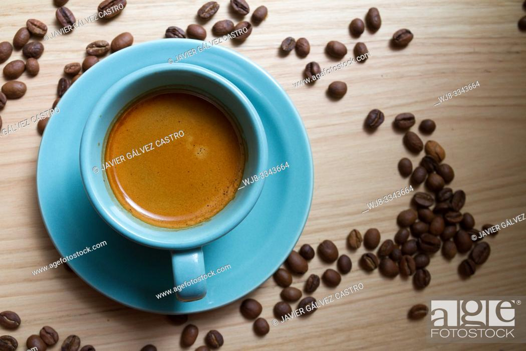 Stock Photo: White porcelain cup with expresso coffee, on wooden board decorated with roasted coffee beans.