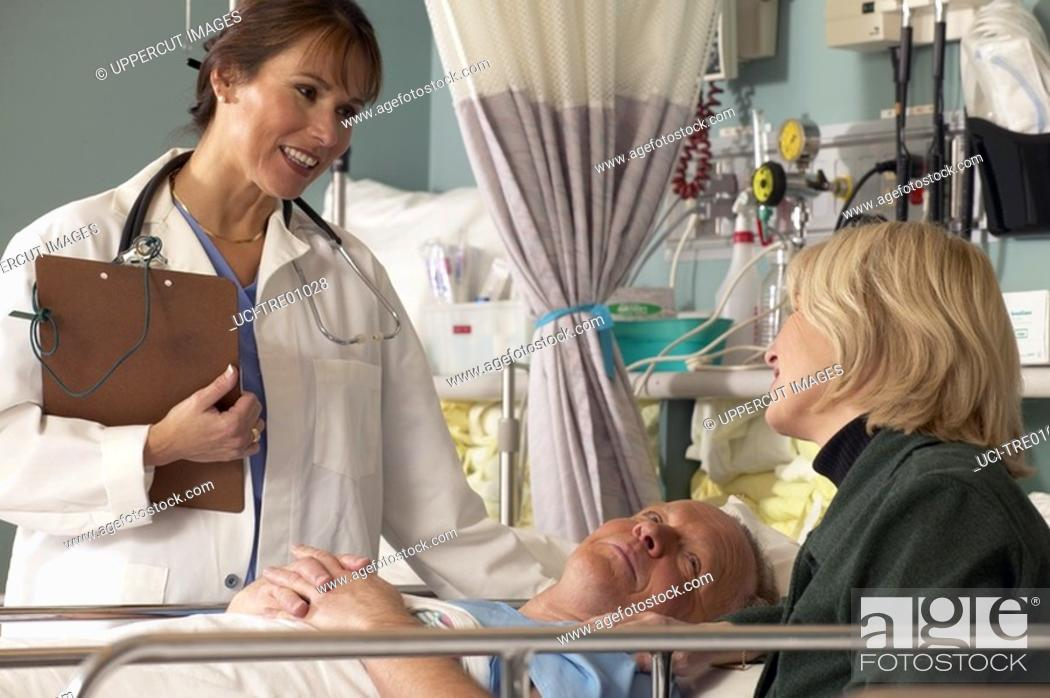 Stock Photo: Female doctor talking to patient and his wife.