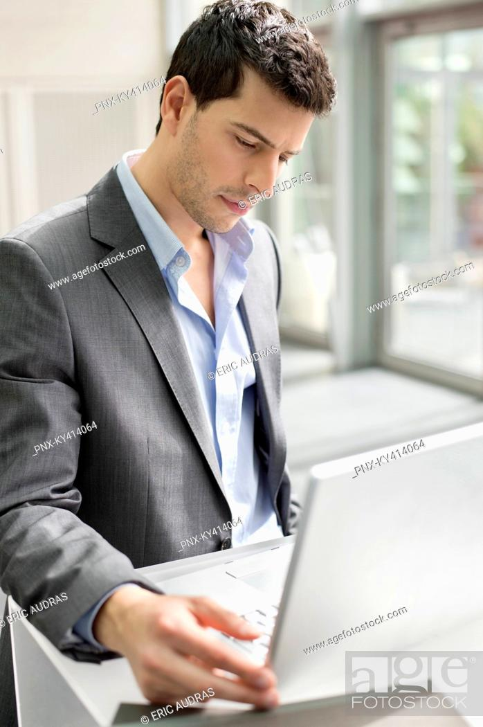 Stock Photo: Businessman working on a laptop in an office.