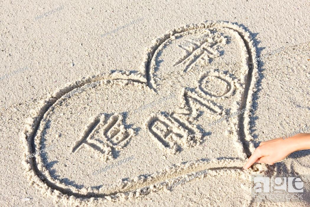 Stock Photo: Person's hand drawing heart shape on the beach.