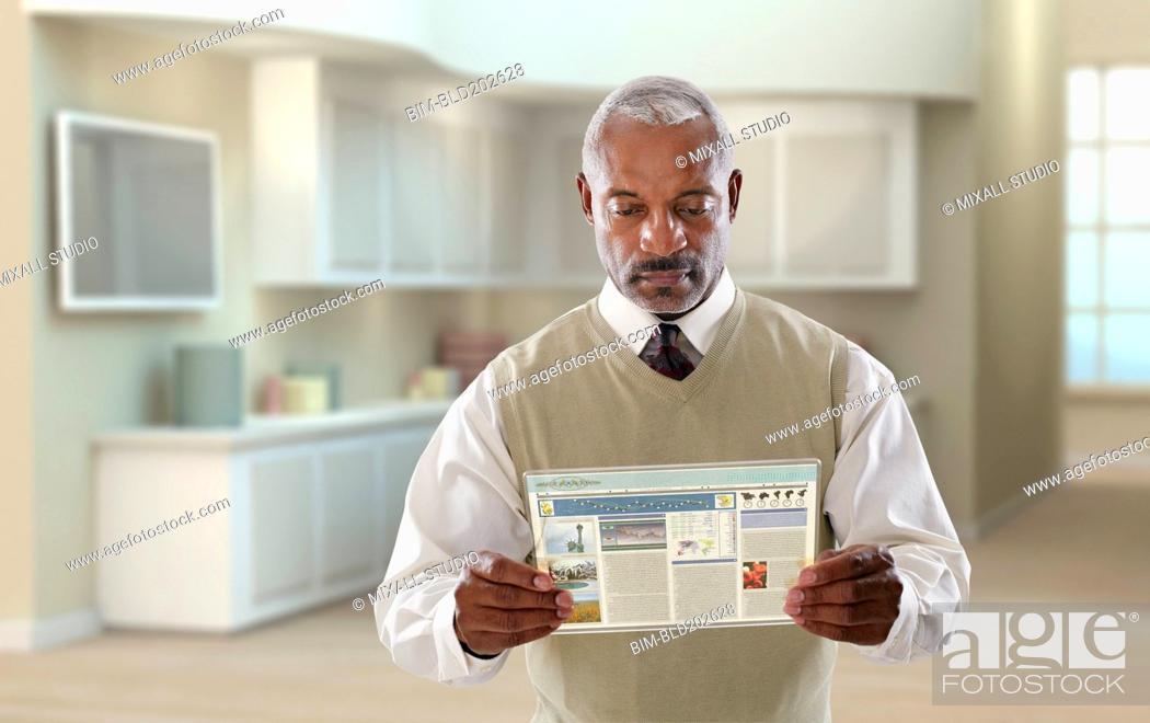 Stock Photo: Black businessman using digital tablet in office.