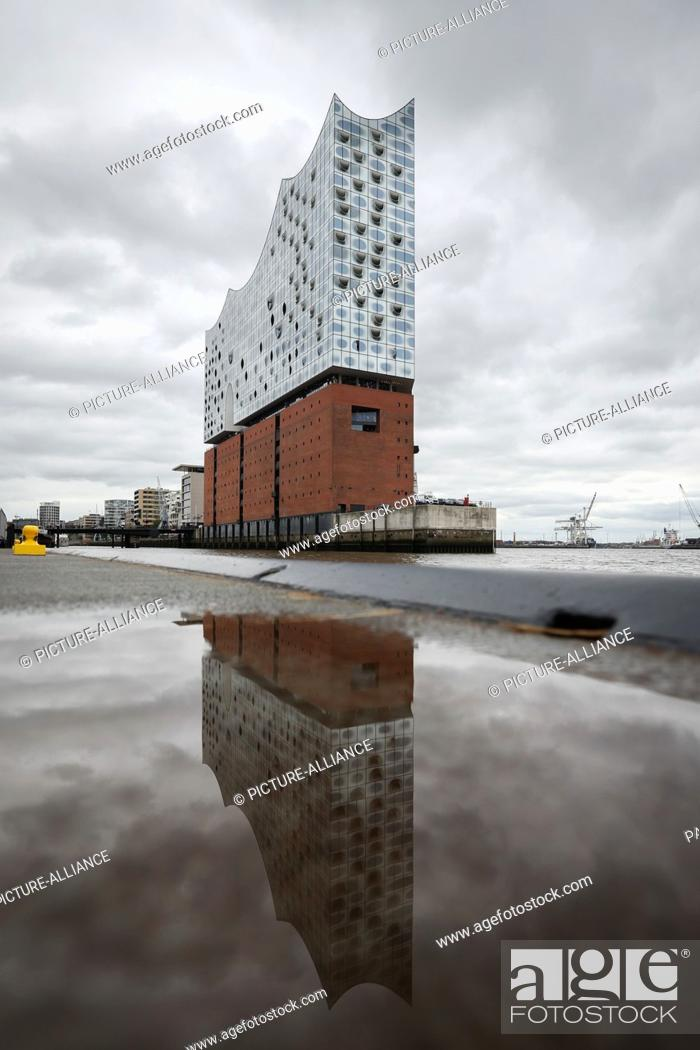 Stock Photo: 13 September 2021, Hamburg: The imposing building of the Elbphilharmonie in Hafencity is reflected in a puddle on a pier.