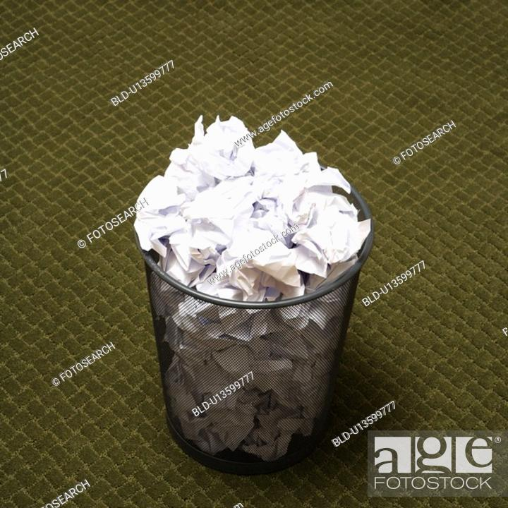 Stock Photo: Wire mesh trash can filled with crumpled paper on green carpet.