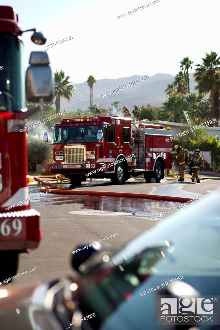 Stock Photo: A fire truck and firefighters on a suburban street next to a burning house.