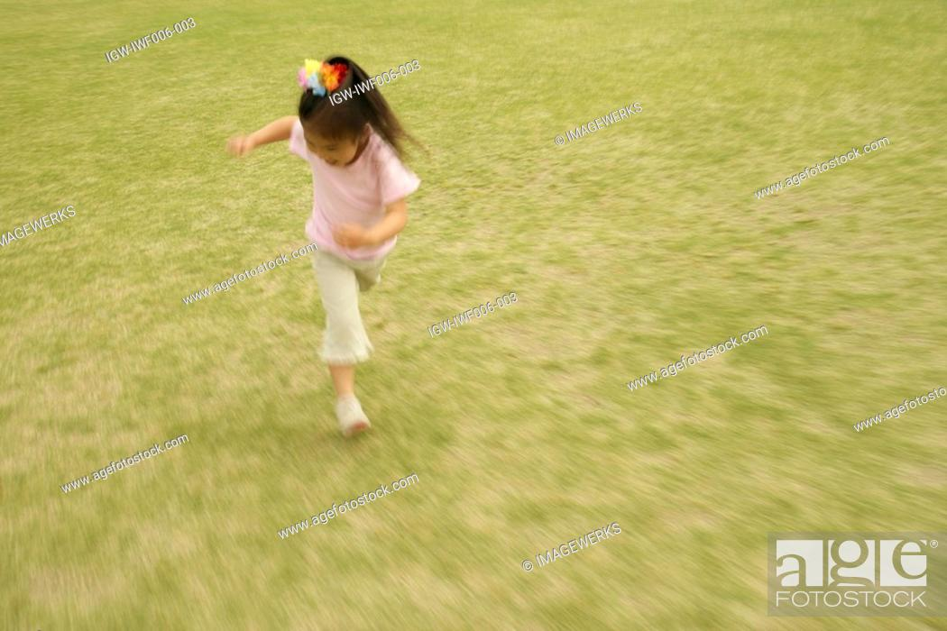 Stock Photo: A girl running on a vast grassland.