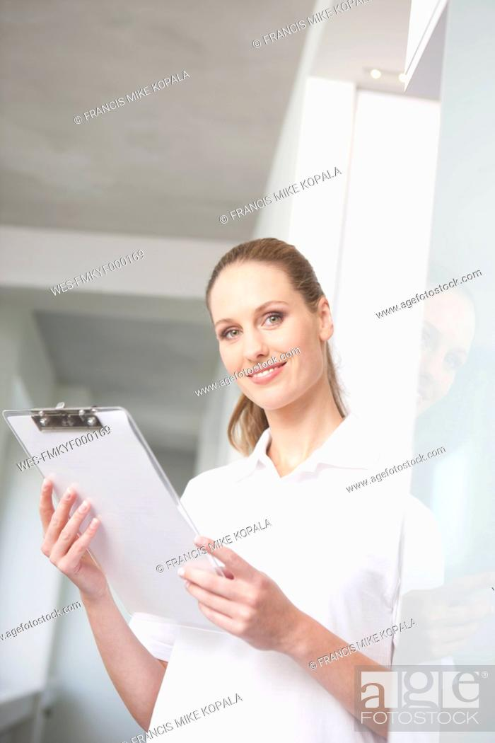 Stock Photo: Germany, Dentist holding clip board.