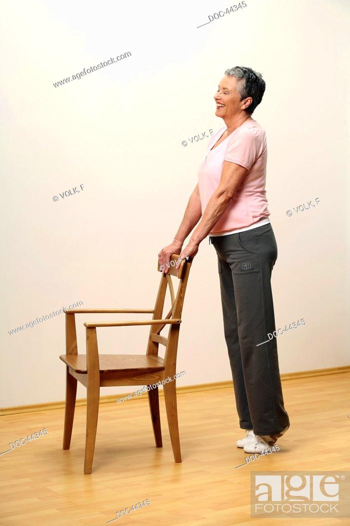 Imagen: older woman doing gymnastics with a chair - woman is standing on tiptoe - pumping - muscularity - senior.