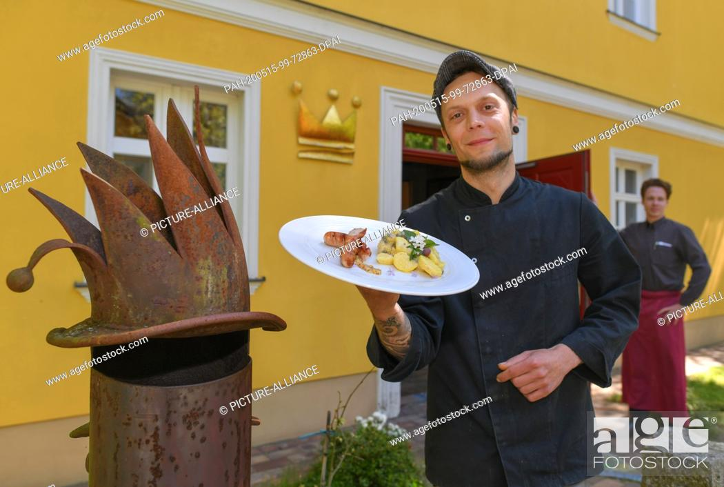Stock Photo: 15 May 2020, Brandenburg, Kaisermühl: Sören Horny, chef at Hotel Kaisermühle, shows wild garlic sausages with potato caper salad on a plate.