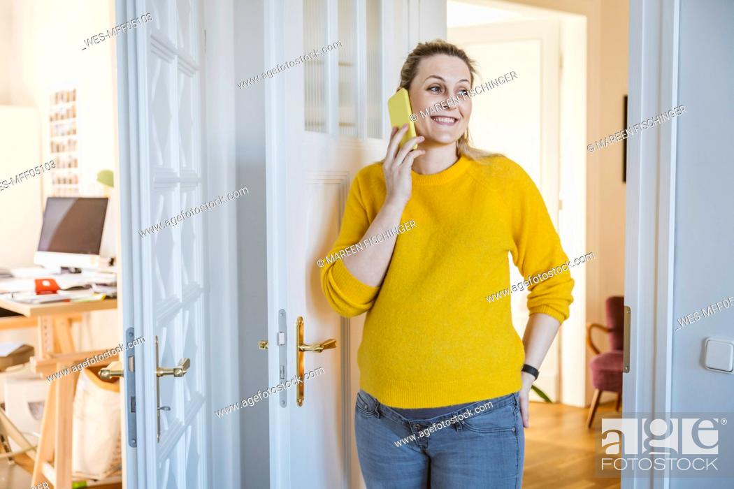 Imagen: Pregnant woman at home talking on the phone.