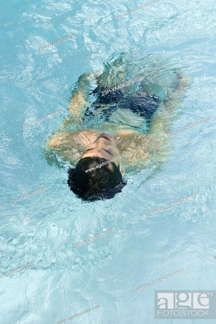 Stock Photo: Man floating on back in pool, rear view.