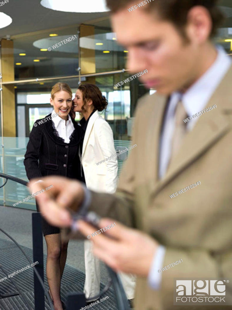 Stock Photo: Two businesswomen whispering, man using palmtop (focus on background).