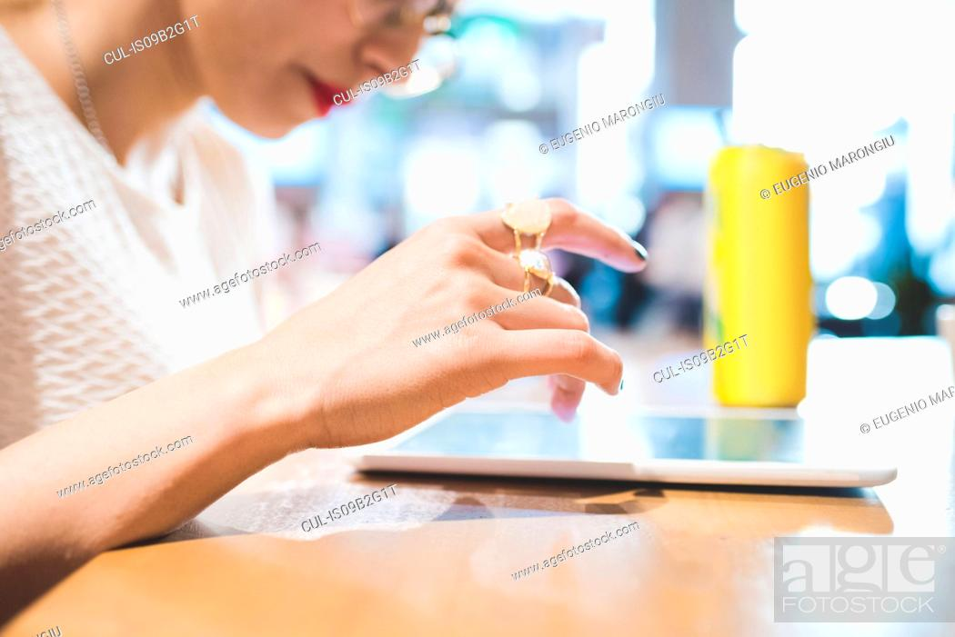 Stock Photo: Woman at table using digital tablet, Milan, Italy.