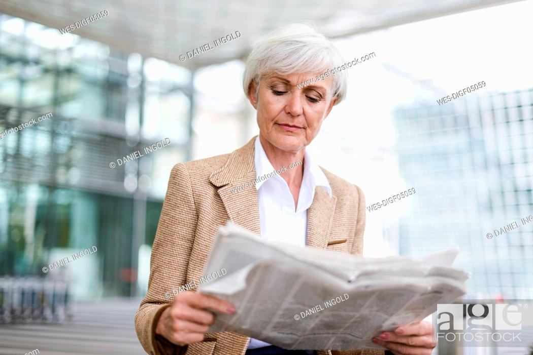 Stock Photo: Senior businesswoman in the city reading newspaper.