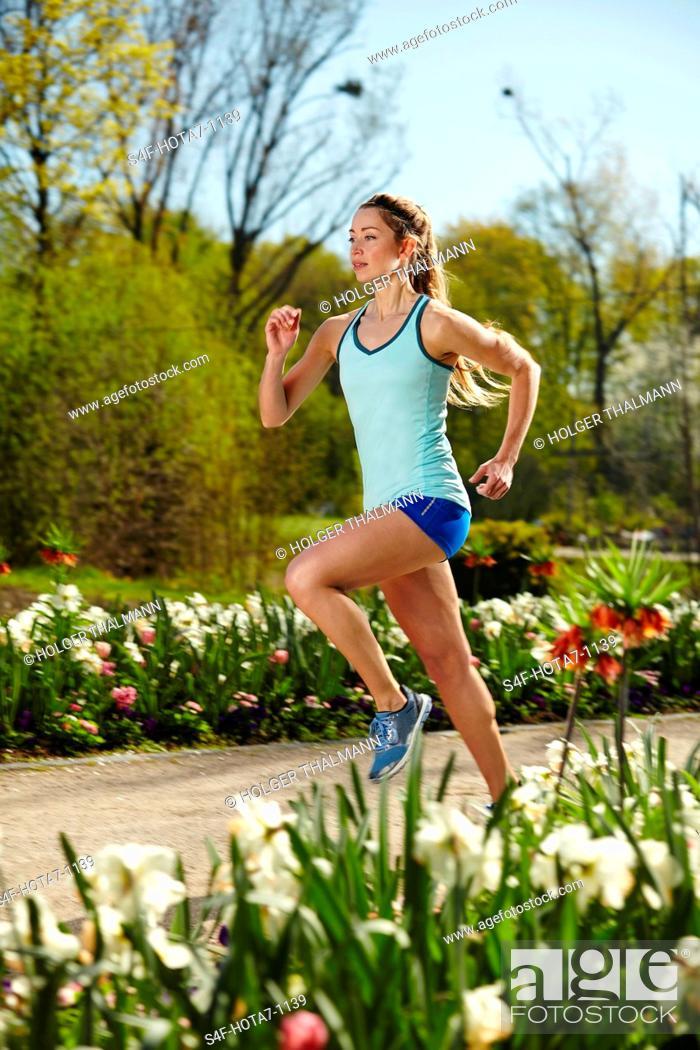 Imagen: Sportliche Frau läuft in einem Park im Frühling.