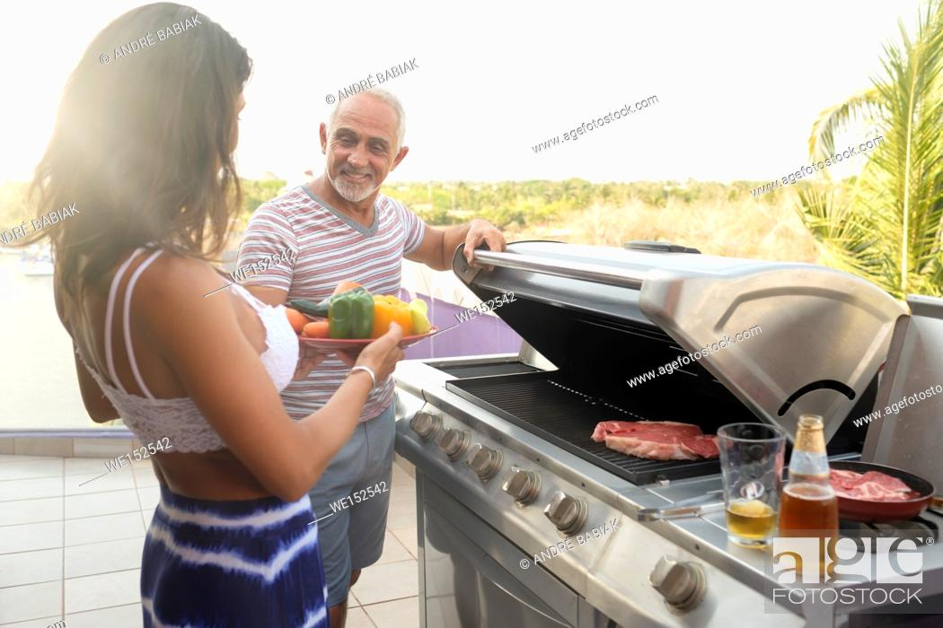 Stock Photo: Woman bringing vegetables to a man grilling some meat outdoors.