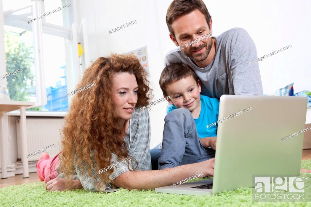 Stock Photo: Germany, Berlin, Family using laptop on floor.