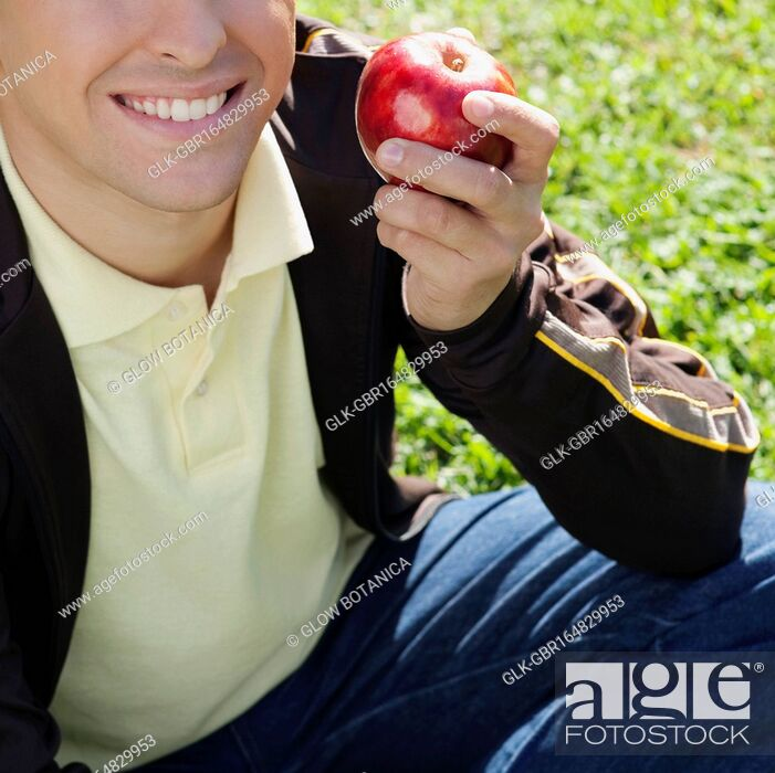 Stock Photo: Close-up of a man holding an apple and smiling.