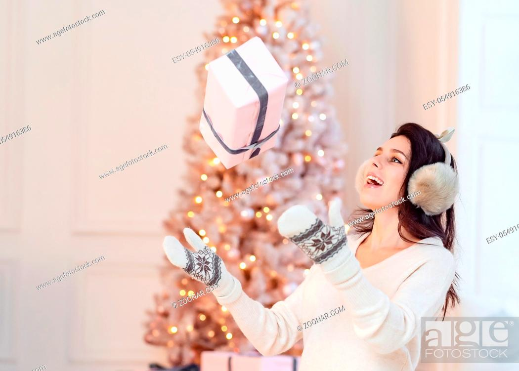 Imagen: Beautiful young girl in white dress posing on camera. Christmas concept.