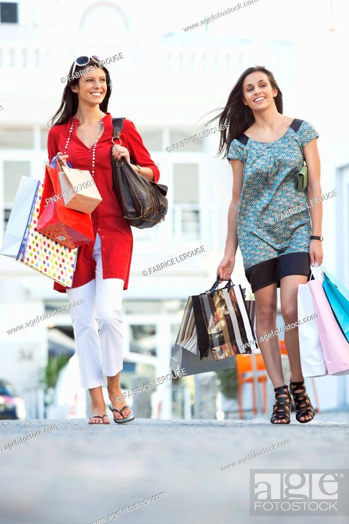 Stock Photo: Two young women walking with shopping bags.