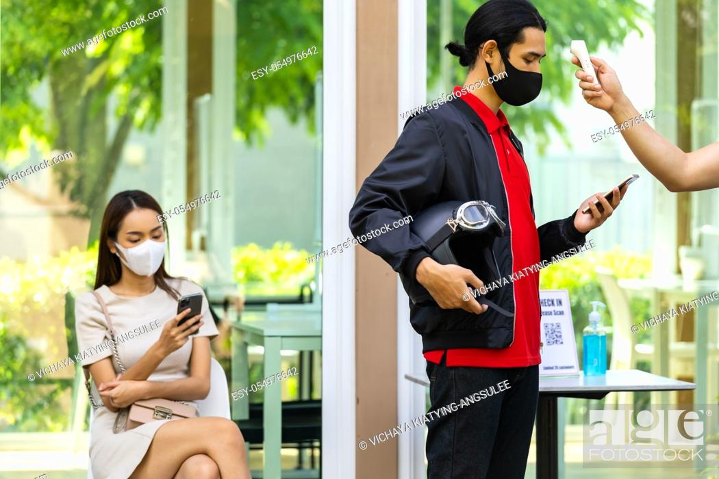 Stock Photo: Take Temperature for customer with face mask before getting in restaurant with social distance queue in line new normal after coronavirus covid-19 pandemic.