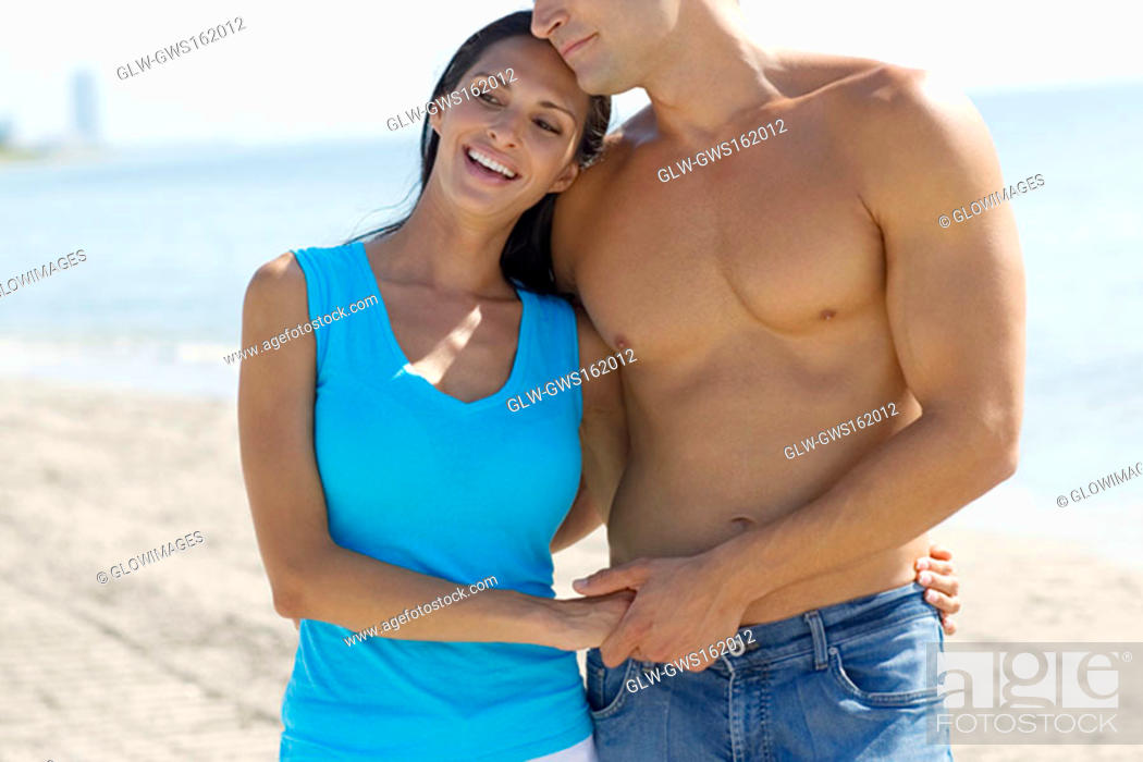 Stock Photo: Close-up of a young couple standing on the beach.