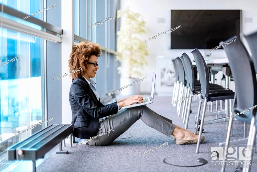 Stock Photo: Smiling young businesswoman sitting on the floor in conference room using laptop.