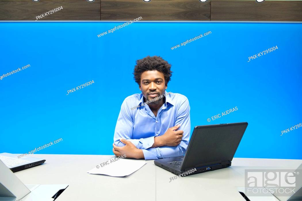 Stock Photo: Businessman smiling with a laptop in a conference room.