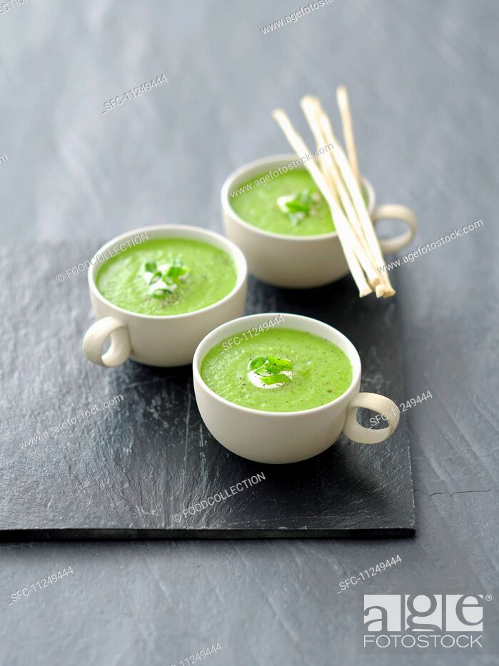 Stock Photo: Cream of pea soup with grissini.