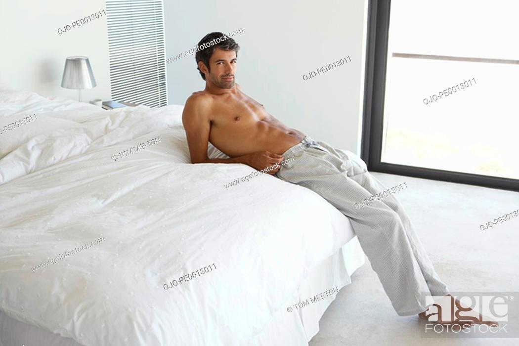 Stock Photo: Man reclining on bed.