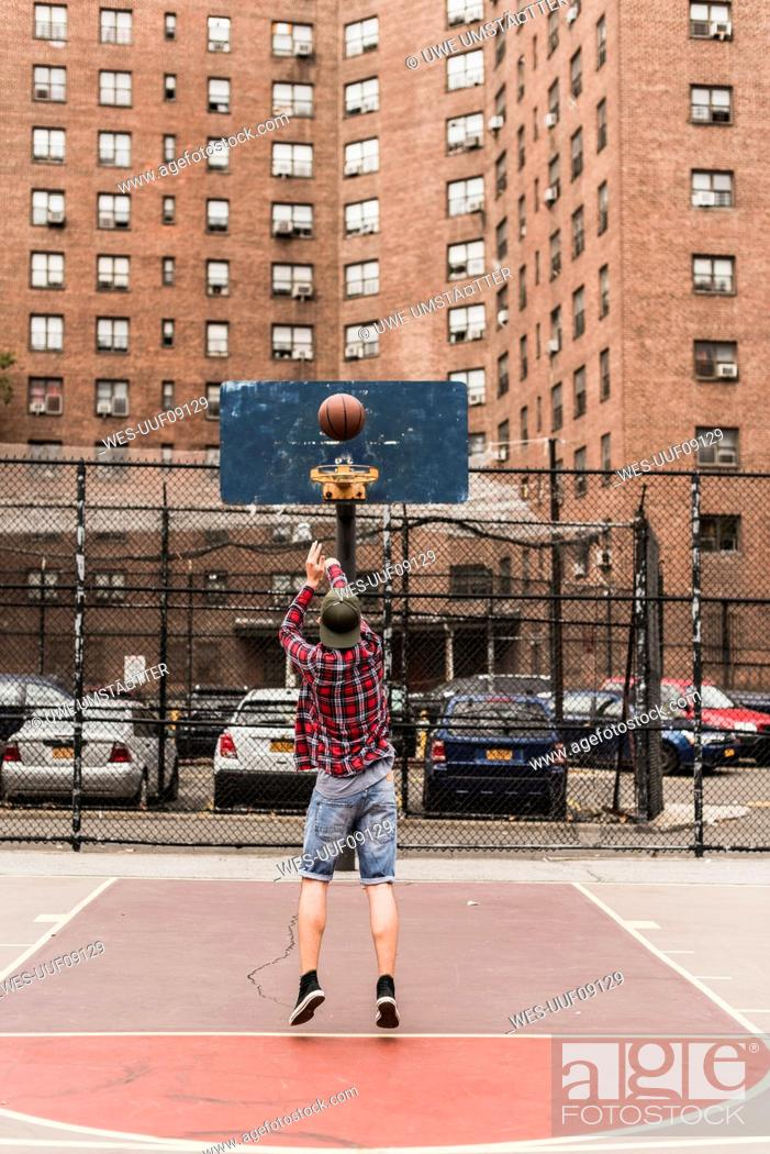 Stock Photo: Young man playing basketball on an outdoor court.