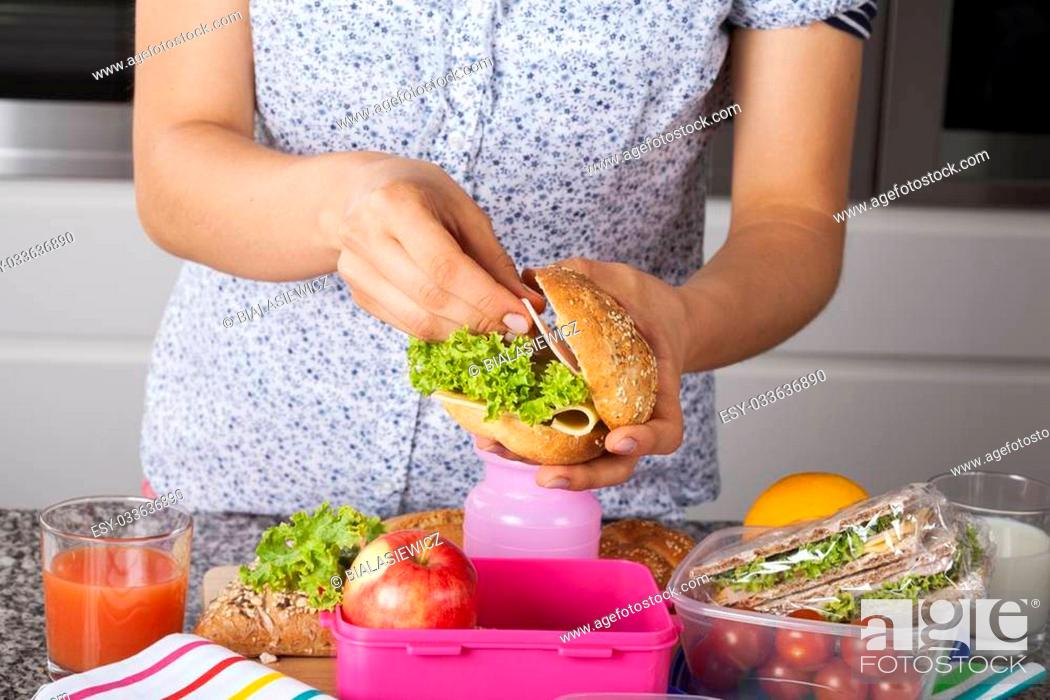 Stock Photo: Mum preparing her child second meal for school.