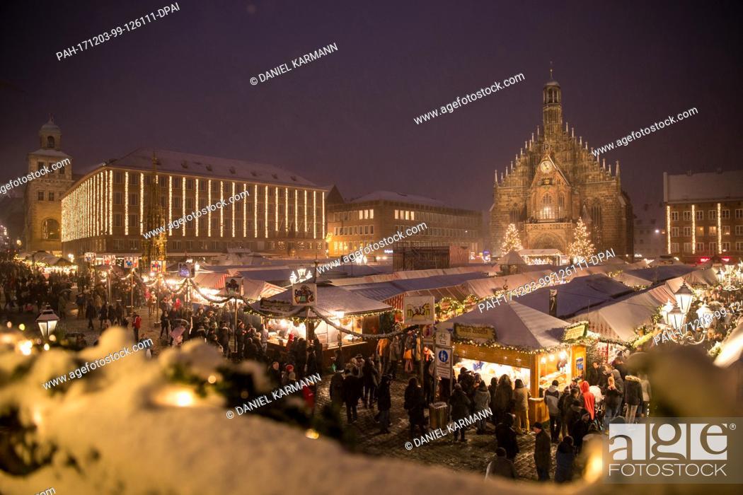Stock Photo: Visitors walk across the Christkindlesmarkt during snowfall in Nuremberg, Germany, 03 December 2017. Photo: Daniel Karmann/dpa.