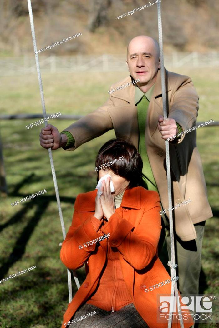 Stock Photo: Mature man pushing woman on swing while she blowing her nose.