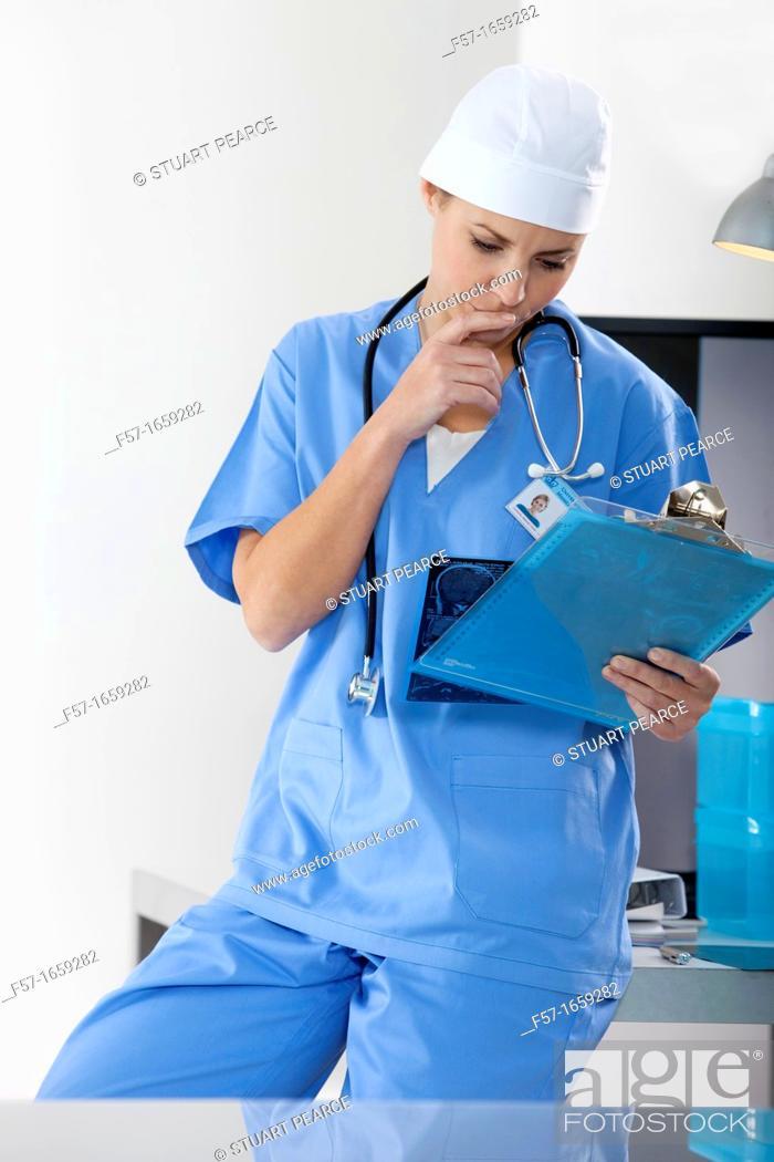 Stock Photo: Female Nurse examining an X-ray.