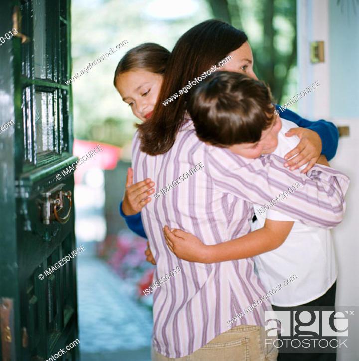 Stock Photo: Mother hugging her children in doorway.