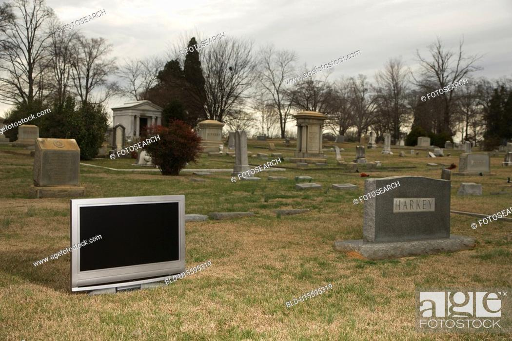 Stock Photo: Flat panel television set in cemetery next to headstone.