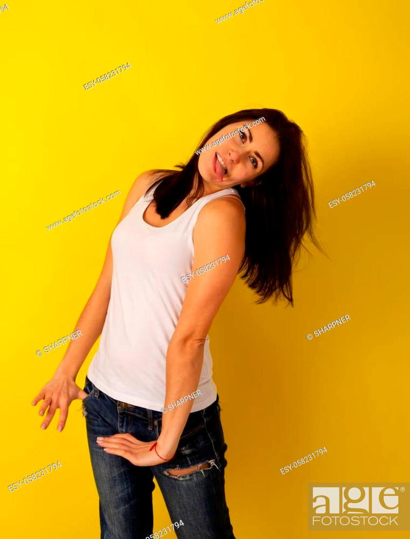 Stock Photo: Pretty girl with dark hair in casual clothes in good mood makes a wry face and makes a face on a bright yellow background.