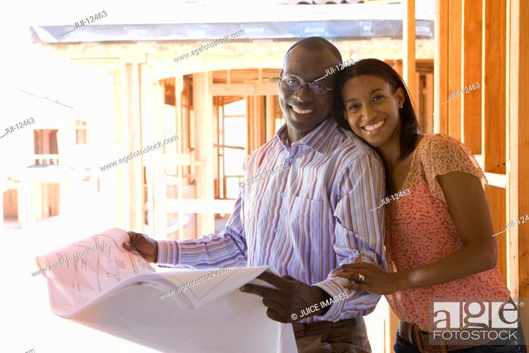 Stock Photo: Young couple with blueprints in partially built house, smiling, portrait.