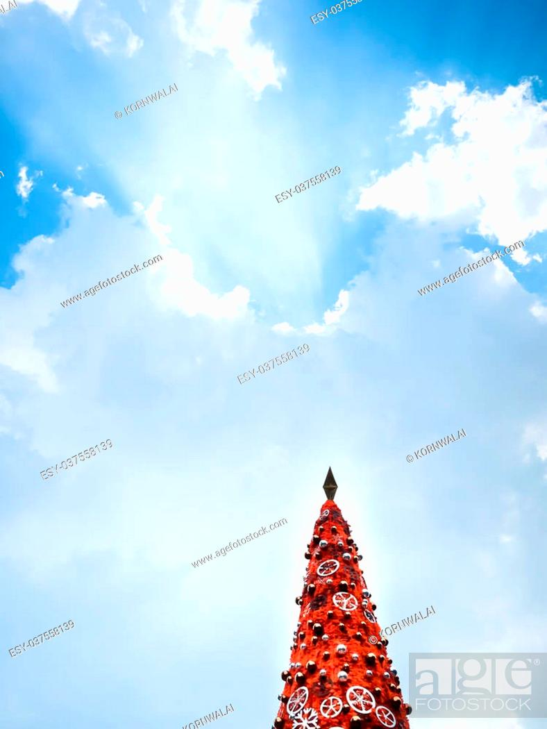 Stock Photo: Beautiful decorated christmas tree with star and sparkle ball on Blue sky and beautiful clouds.